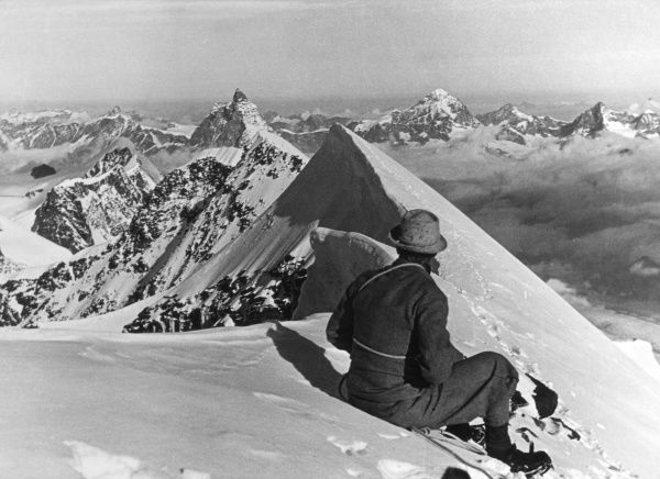 A mountaineer, perched on the snow covered summit of Monte Lyskamm, Cervinia, Italian Alps. Date: 1930s