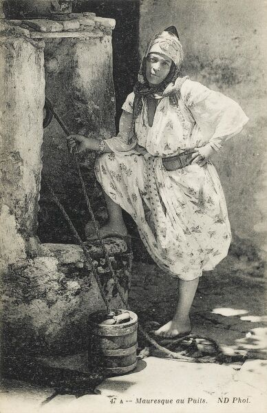 A Moorish Algerian woman raising water from a well in a small wooden bucket