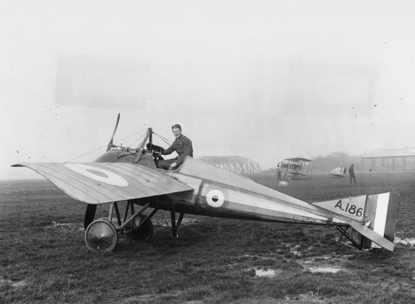 A Morane-Saulnier Type N French monoplane fighter aircraft, with Lieutenant Bayetto of the RFC (Royal Flying Corps) in the cockpit during the First World War. In the background is a Henry Farman biplane (dating from 1910-1911) with a 50hp Gnome engine