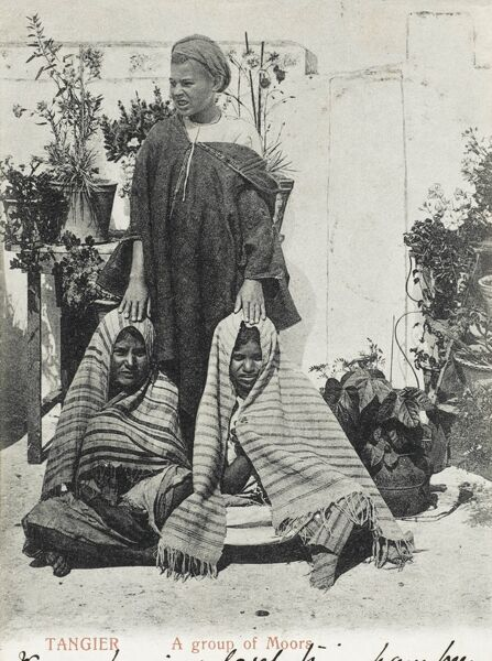 A Moorish man with two of his wives in an outdoor garden in Tangiers, Morocco