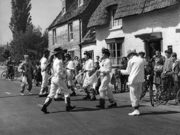 MORRIS DANCING: Bampton, Oxfordshire. Villagers watch a morris dancing team perform in the middle of a road outside a pub on a sunny Whit Monday. Date: circa 1950