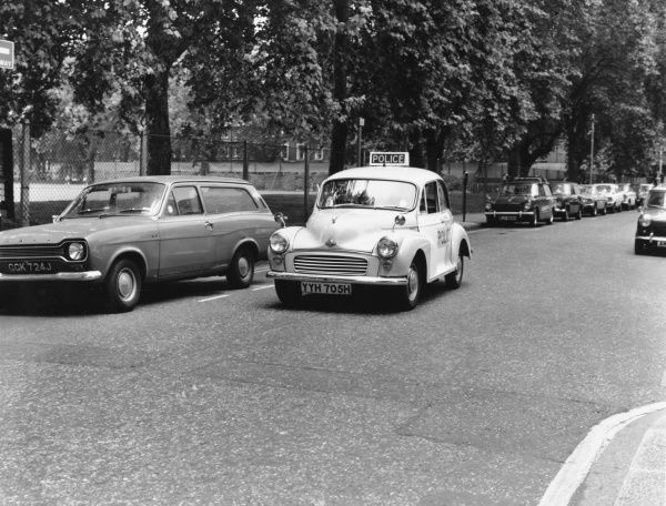 A Morris Minor police car making its way along a London street