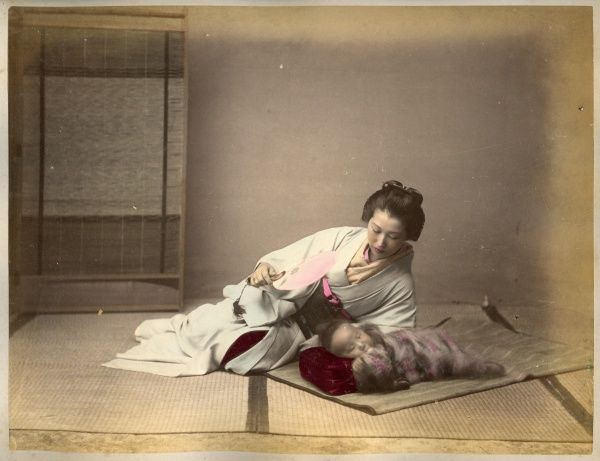 A young Japanese mother fans her baby to keep him cool as he lies sleeping on a mat on the floor