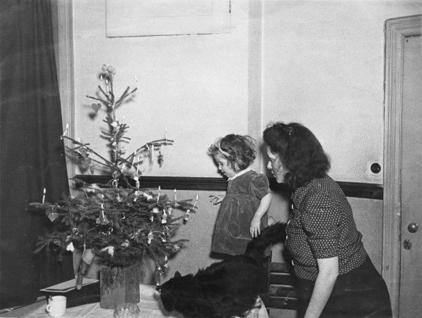 A mother and her little daughter admire their Christmas tree. It has lit candles, and sweets hanging from the branches. A black cat seems quite interested too