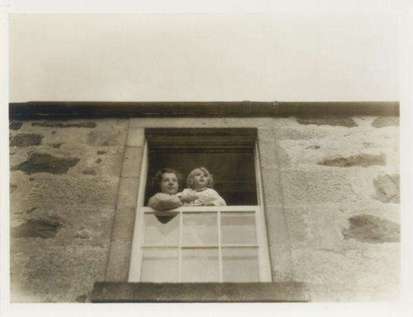 A mother and her daughter looking out of a bedroom window somewhere in Scotland