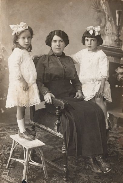 A mother and her two daughters pose for their photograph. One daughter sits on the arm of her mother's chair, while the other daughter stands on a stool. The girls are wearing identical white lacy dresses, with a large white ribbon in their hair