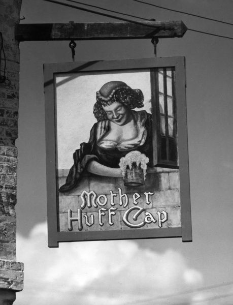 The splendid sign of the 'Mother Huff Cap' pub, depicting a strapping wench serving a flagon of frothy ale, Great Alne, Warwickshire, England. Date: 1950s