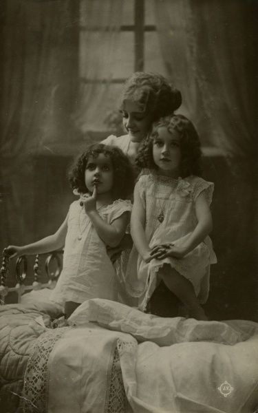A mother and her two little girls at bedtime.  1917