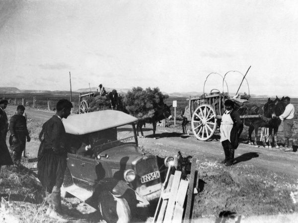 A motor car stuck in a ditch on the road from the port of Larnaca to Nikosia, Cyprus. The rough, narrow dirt tracks are really only fit to be used by traditional donkey carts. Date: 1930s