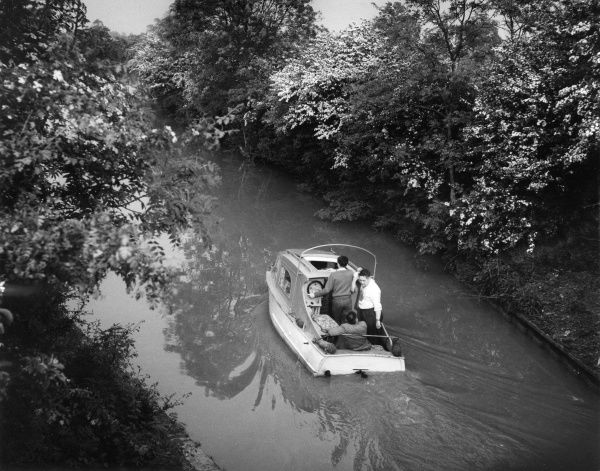 A small 'cruiser' motor boat on the Grand Union Canal at Bugbrooke, Northamptonshire, England, passing through high banks of flowering hawthorne. Date: early 1960s