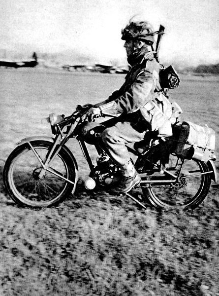 Photograph showing a soldier, of the Motorcycle Section of the British First Airborne Division, heading off on his motorcycle, 1944
