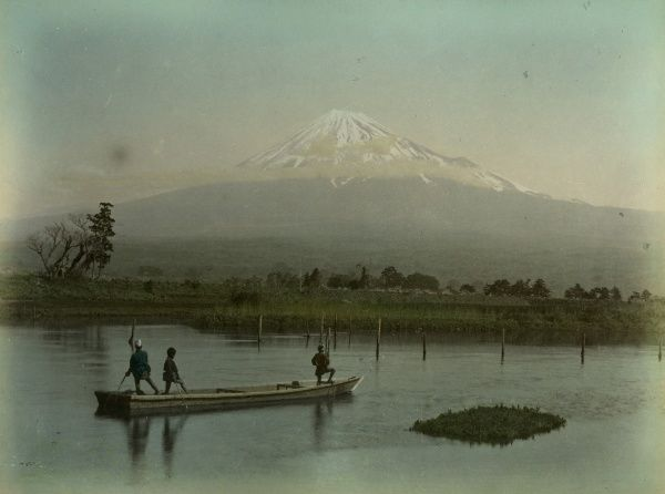 Three Japanese men, perhaps fishermen, in a boat with Mount Fuji in the background