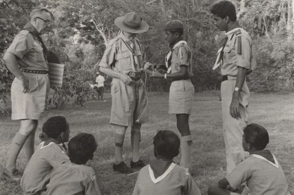 Mr D.F. Morgan (Commonwealth Commissioner) in Aden talking to a Yemeni Scout with other scouts sitting on the floor watching. circa 1959