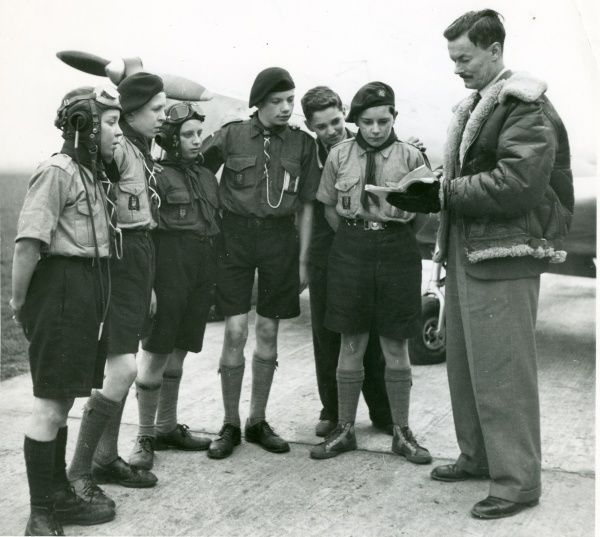 Six Air Scouts stand listening to Mr Trevor Scott-Chard talk about aviation, with a plane visible in the background. circa 1950s