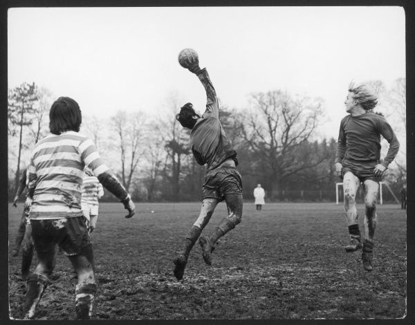 An amateur game of football played on a very muddy pitch: the goalkeeper catches the ball in mid-air