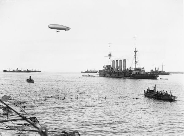 A view of Mudros Harbour on Lemnos Island off the Turkish coast, with a British airship passing ovehead during World War I