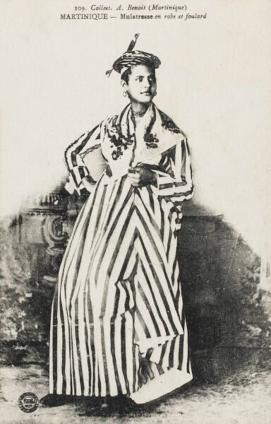 A beautiful Mulatto (person with one white parent and one black parent, or a person who has black ancestry and white ancestry) woman in a Foulard dress (foulard is a lightweight fabric, either twill or plain-woven, made of silk or a mix of silk