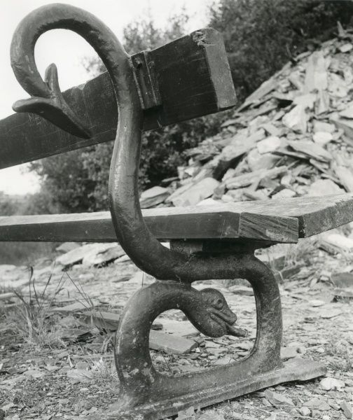 Close-up view of a municipal bench with a decorative iron dragon support, in the Nantlle Valley, North Wales. A pile of slate waste indicates that the bench is not far from a closed-down slate quarry