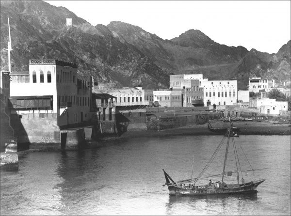 View of the harbour at Muscat, capital of Oman, with a boat in the foreground. Photograph by Ralph Ponsonby Watts