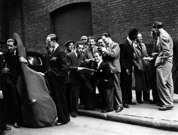 A diverse group of unknown musicians and actors, including a dwarf, chatting in the street probably outside a venue in London. One man has a double bass. Date: C.1950