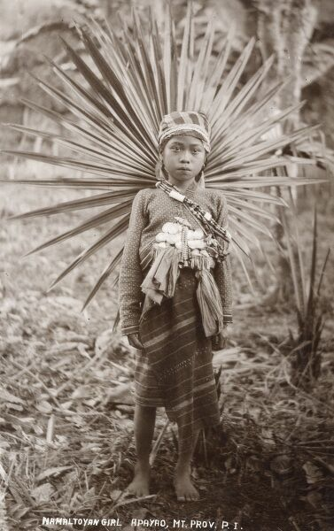 Namaltoyan Girl - Apayao - Mountain Province, Philippines. Apayao is a landlocked province of the Philippines in the Cordillera Administrative Region in Luzon. This pretty young girl is in a very fine costume, incorporating a sunburst of leaves on her back