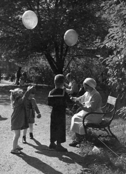A uniformed nanny sits on a park bench while the children in her charge, including a boy in a sailor suit, play with their balloons