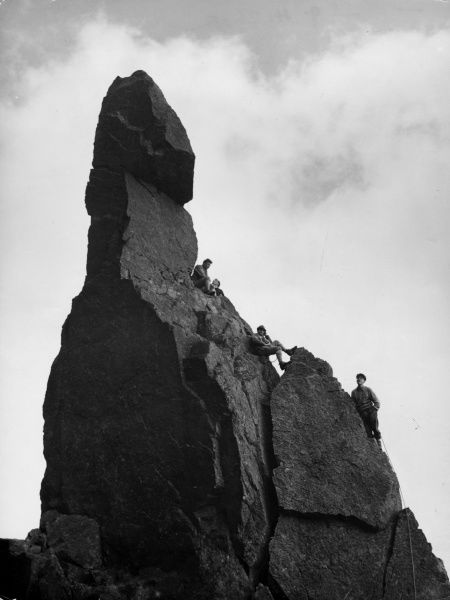 Rock climbers larking about on Napes Needle, Great Gable, Lake District, Cumbria, England. Date: 1950s