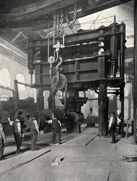 Male workers are dwarfed by the massive Nasmyth hammer at the Atlas Steel Works, Sheffield, South Yorkshire. Date: circa 1902