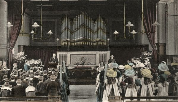 The Birmingham branch of the home and orphanage run by the National Children's Home (NCH). Here, the children are attending morning prayers. A large pipe organ dominates the hall. Date: Date unknown