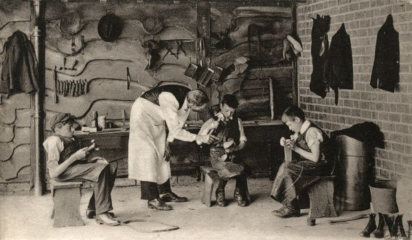 The Birmingham branch of the home and orphanage run by the National Children's Home (NCH). Here, boys in aprons and surrounded by the tools of the trade are learning the craft of shoe-making. Date: Date unknown