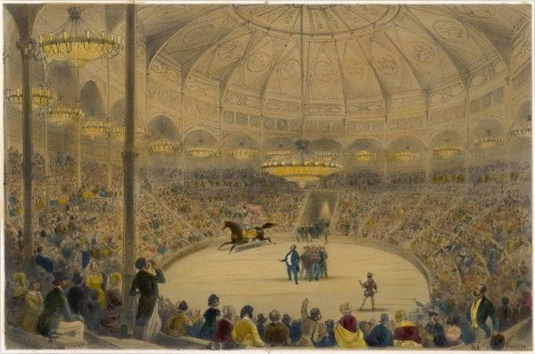 An interior view of the Cirque National in the Champs Elysees, Paris. You can see the magnificent roof as a woman stands on a horse's back & canters round the ring