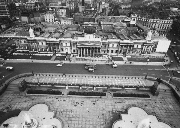 A fine aerial view of the National Gallery and fountains in Trafalgar Square, London. Note the road in front of the Gallery, before it was pedestrianised. Date: 1960s