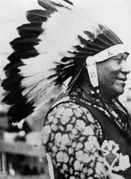 A Native American ('Red') Indian wearing a traditional head-dress. Date: 1930s