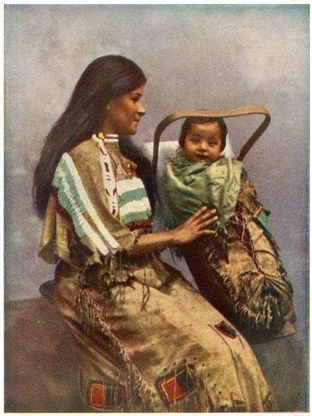A native American mother holds her papoose in its carrying basket