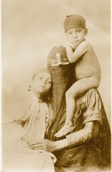 A touching family group photograph of a heavily-veiled native Egyptain Mother and her two young children, one sitting on her shoulders. The roll above the veil is to hide the nose from sight