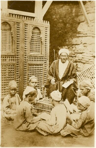 A 'Native' School in Cairo, Egypt. Children gather around the teacher of the lesson, beside a finely cut Wooden screen