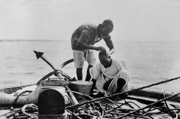 A barber gives his client a haircut on board a boat on the White Nile, Sudan, North Africa. Date: early 1930s