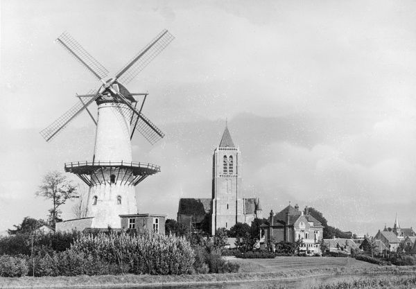Tholen, in the Zeeland province of the Netherlands, with its typical Dutch windmill and church tower. Date: early 1930s