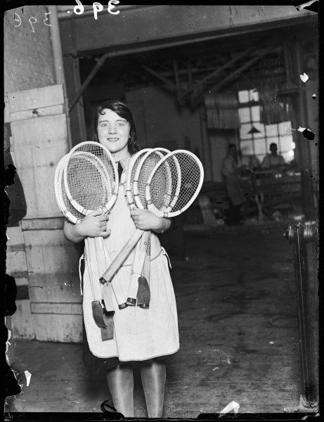 A female worker shows off several newly made tennis racquets, Wimbledon, London