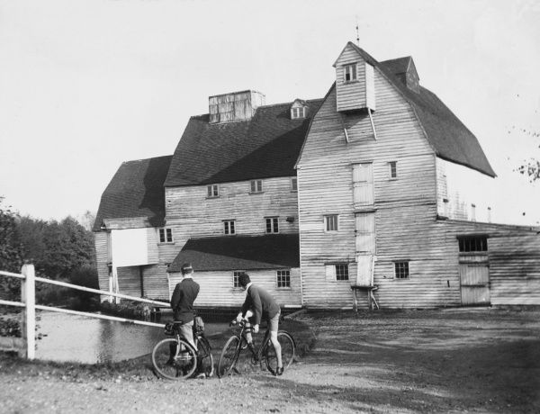 Two young men, cyclists, take time out to stop and admire the splendid weatherboarded Newark Watermill, Pyrford, Surrey, England