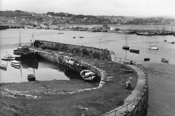 The lovely sweeping curve of the harbour wall at Newlyn, a picturesque fishing village near Penzance, Cornwall, England. Date: 1950s