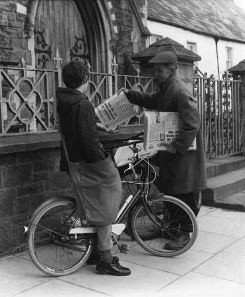 Delivering newspapers on his bicycle, a boy pauses to speak to a colleague. Date: 1950s