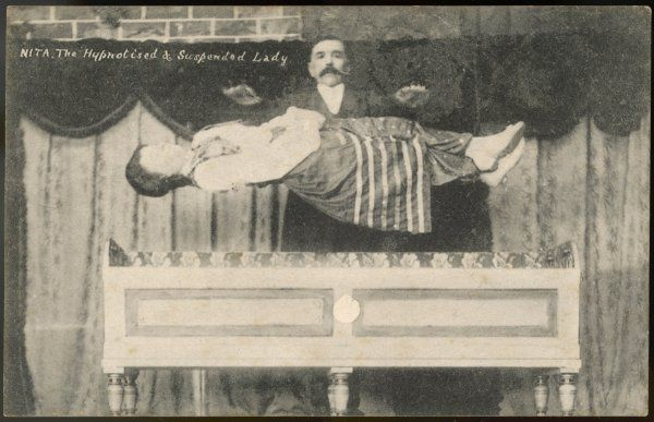 A magician performs a levitation trick on stage: Nita, the hypnotised and suspended lady