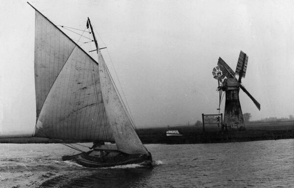 A sign by the windmill points the way to the Lion Hotel on the River Thurne, Norfolk. The sailing boat on the broad certainly seems keen to get home for supper! Date: circa 1930s