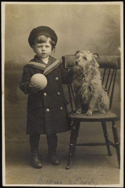 A young boy dressed in a sailor suit and holding a ball poses for a studio portrait with his pet dog, a grizzled looking terrier