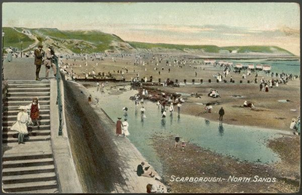 View of the North Sands at Scarborough, North Yorkshire, with strollers and paddlers