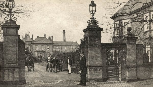 A uniformed porter at the gate of the Northern Hospital at Winchmore Hill, Enfield, Middlesex