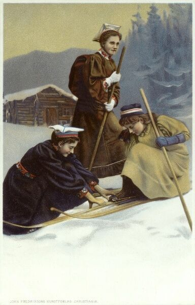 A Norwegian girl helps a friend put on her cross country skis. Another friend is ready to go behind. Date: circa 1906