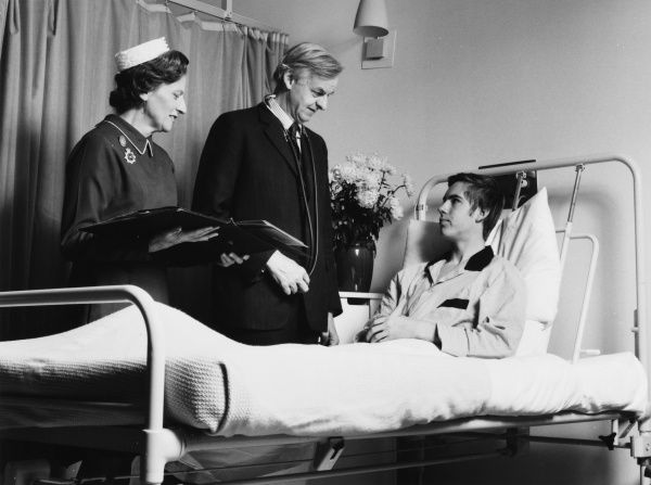 Scene at the Metropolitan Police Medical Centre, Hendon, north west London, with a nurse (probably matron) and a doctor attending to a patient