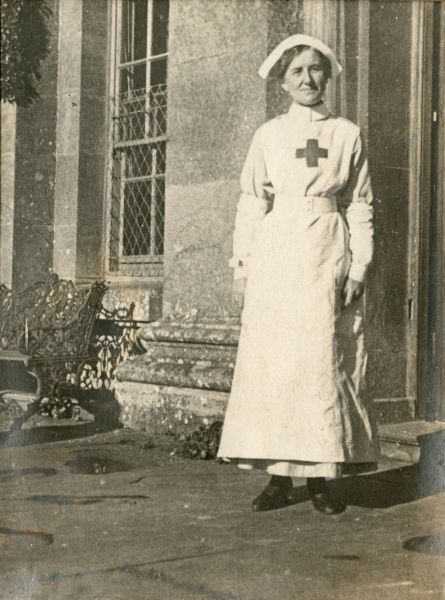 A nurse in uniform standing in the doorway of a hospital building
